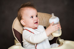 Baby drinking milk from a bottle in the apartment Stock Photo
