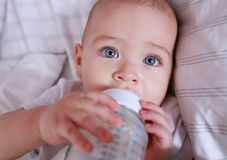 Baby drinking milk from bottle in bed. Cute baby drinking milk from a bottle in a white crib. Stock Photo