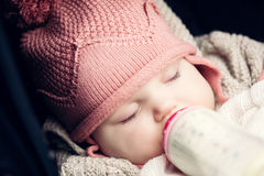 Baby drinking milk from the bottle with her eyes closed. Stock Photos