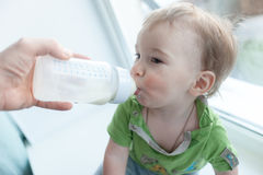 Baby drinking milk from bottle. holding himself. sweet funny Royalty Free Stock Images