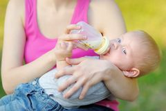 Baby drinking milk from bottle in mother hands Royalty Free Stock Image