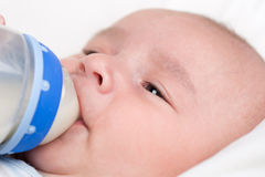 Baby drinking milk from bottle Stock Images