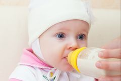 Baby is drinking milk from bottle Stock Images
