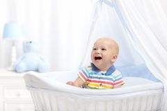 Baby drinking milk. Boy with formula bottle in bed. Baby drinking milk in white crib. Infant boy with formula bottle in bed. Kids nutrition. Healthy food and stock image