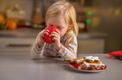 Baby drinking milk with christmas cookies Stock Photos
