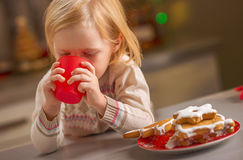 Baby drinking milk with christmas cookies Royalty Free Stock Photo