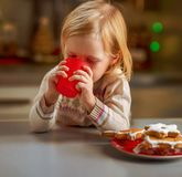 Baby drinking milk with christmas cookies in kitchen Royalty Free Stock Image