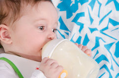 Baby drinking milk formula from a bottle Royalty Free Stock Photos