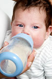 Baby drinking milk of her bottle Stock Image