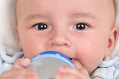 Baby drinking milk and holding the bottle Stock Photos