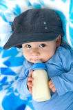 Baby drinking milk. Little cool baby is sleep with a bottle in his hand on a blue blanket and drinking milk from the bottle stock photography