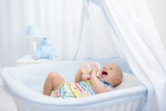 Baby drinking milk. Boy with formula bottle in bed. Baby drinking milk in white crib. Infant boy with formula bottle in bed. Kids nutrition. Healthy food and stock photos