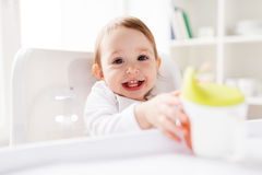 Baby drinking from spout cup in highchair at home Stock Image