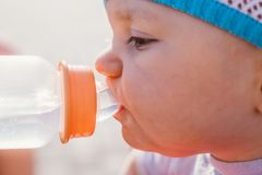 Baby drinking water from a baby bottle for a walk. Face close stock images