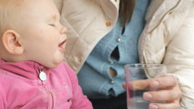 Baby drinking water from glass from mother`s hand stock video