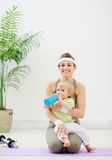 Baby drinking water at mother laps at gym Royalty Free Stock Photos
