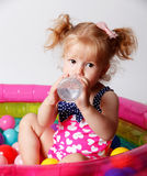 Baby drinking water in the pool Stock Photo