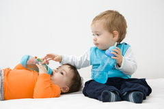 Baby drinks. Together in bad Royalty Free Stock Image