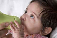 Baby drinks from baby-bottle. Baby Girl Is Drinking From A Baby-bottle Royalty Free Stock Photo