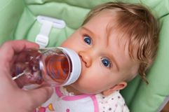 Baby drinks from bottle. Cute baby girl drinks juice tea from a bottle Royalty Free Stock Photos