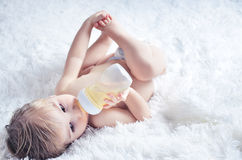 Baby drinks from bottle. Nnaked baby drinks from a bottle while lying on the bed Stock Image