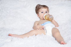 Baby drinks from bottle. Nnaked baby drinks from a bottle while lying on the bed Stock Images