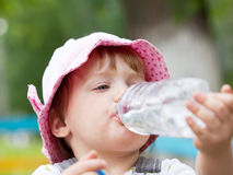 Baby drinks from plastic bottle. 2 years baby drinks from plastic bottle in park Royalty Free Stock Image