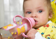 Baby drinks water. I do it myself! Baby drinks water from a bottle with a nipple Stock Image