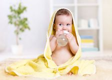 Baby drinks water from bottle wrapped in towel. Baby girl drinks water from bottle wrapped towel at home Royalty Free Stock Photos