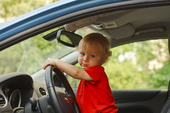 Baby driving. Baby at driver seat holding steering wheel Royalty Free Stock Photography