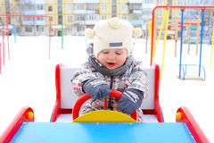 Baby driving car on playground in winter. 17 months baby driving car on playground in winter Stock Photography