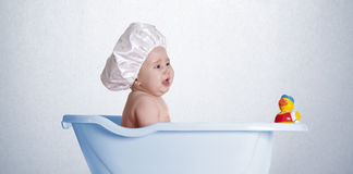 Baby with duck blue. A little baby in her bathtub with her duck stock images