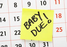 Baby Due Reminder Note. A reminder for when the baby is due written on a yellow paper sticky note and stuck to a wall calendar background Stock Images