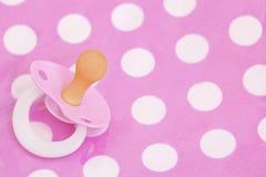 Baby dummy. Pink baby dummy on polka dot background Stock Photo