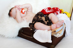 Baby with dummy lies in a suitcase with clothes Royalty Free Stock Photography