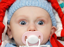 Baby with dummy, looks funny Stock Photography