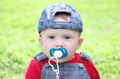 Baby with dummy outdoors. Baby age of 10 months with dummy outdoors Royalty Free Stock Photo