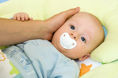 Baby with dummy - pacifier. Three month baby sucking dummy and holding father's hand. Child is looking straight into camera royalty free stock photos