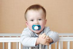 Baby with dummy in white bed Stock Photos