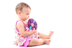 Baby and a DVD. Baby holding a CD or DVD media royalty free stock image