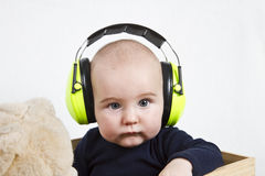 Baby with ear protection. Baby with yellow ear protection in loud environmant. neutral grey background Stock Images