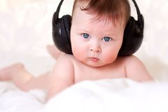 Baby and  earphones Royalty Free Stock Images