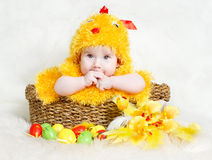 Baby in Easter basket with eggs in chicken hat Stock Photo