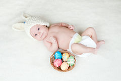 Baby in Easter bunny cap with eggs in basket. Adorable baby dressed in Easter bunny cap with eggs in basket Stock Photography