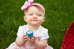 Baby Easter Closeup Smirk. Small child holding a blue Easter egg while smirking stock image