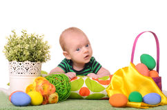 Baby with easter colored eggs. And flowers on white background Stock Images