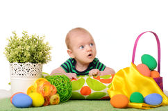 Baby with easter colored eggs. And flowers on white background Stock Photo