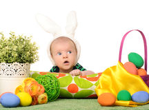 Baby with easter colored eggs. And flowers on white background Stock Photography