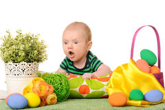 Baby with easter colored eggs. Funny baby with easter colored eggs and flowers on white background Stock Photo