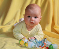 Baby and easter eggs. Infant baby boy with artificial Easter eggs on yellow drapery background Royalty Free Stock Photography
